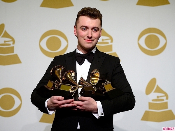 Sam Smith junto a los tres Grammy ganados por él.