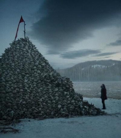 """Imagen de Leonardo Di Caprio frente a una montaña con craneos de bufalos en """"The Revenant""""."""